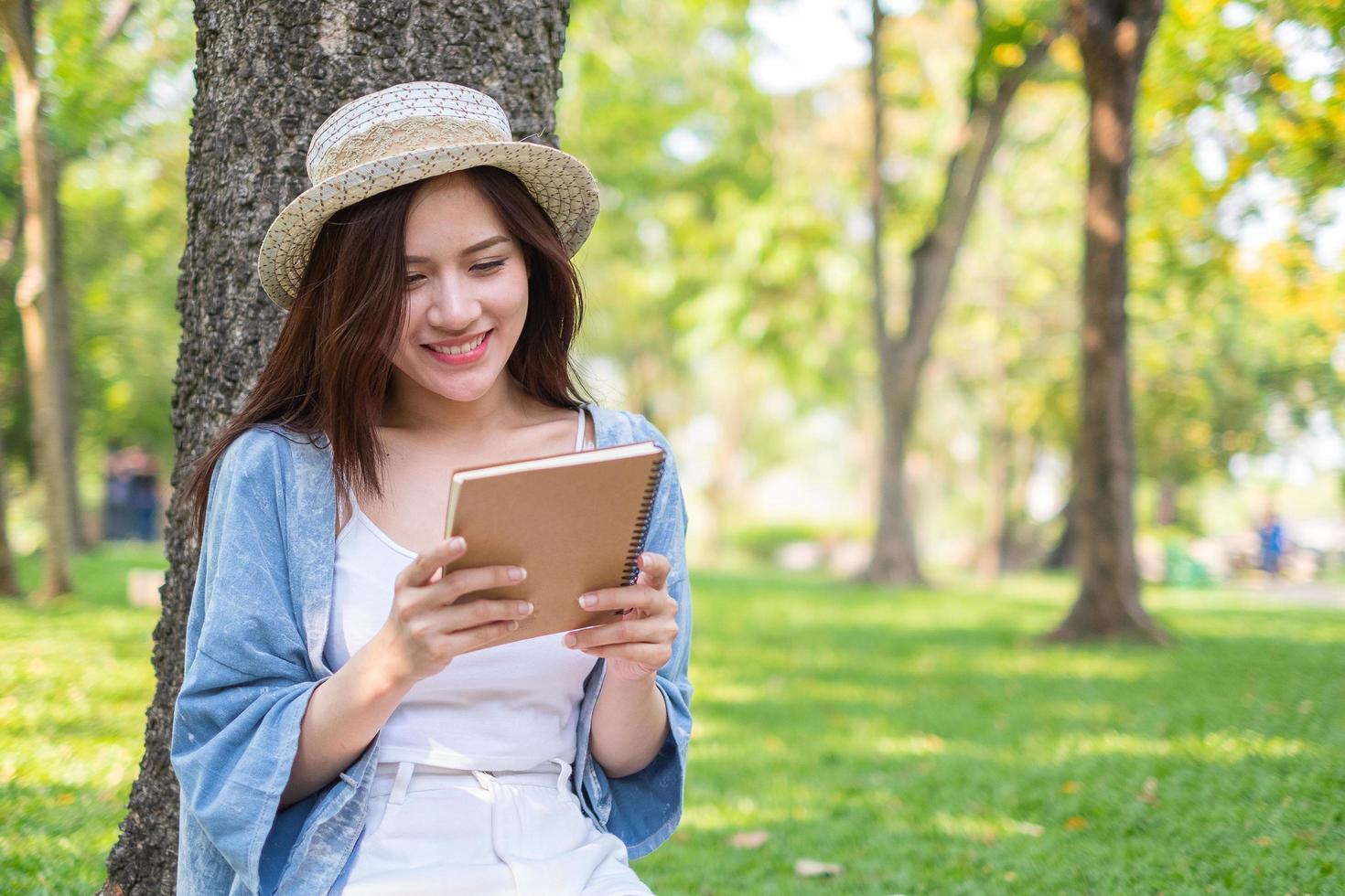 Frau, die Notizbuch im Park betrachtet foto