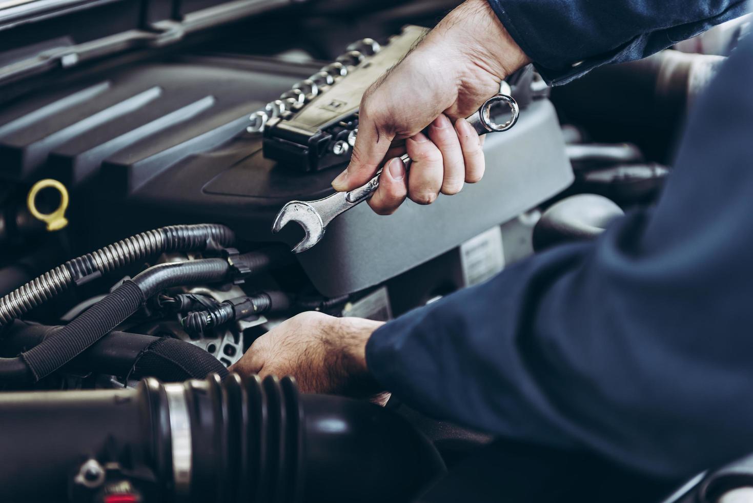 Mann mit Schraubenschlüssel am Automotor foto
