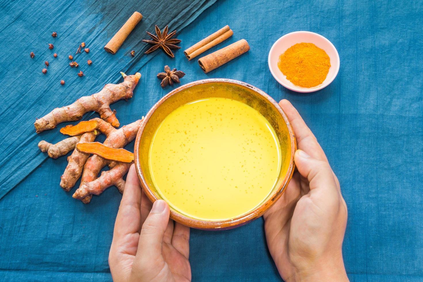 Hände halten goldene Milch oder Kurkuma Latte mit Zutaten foto