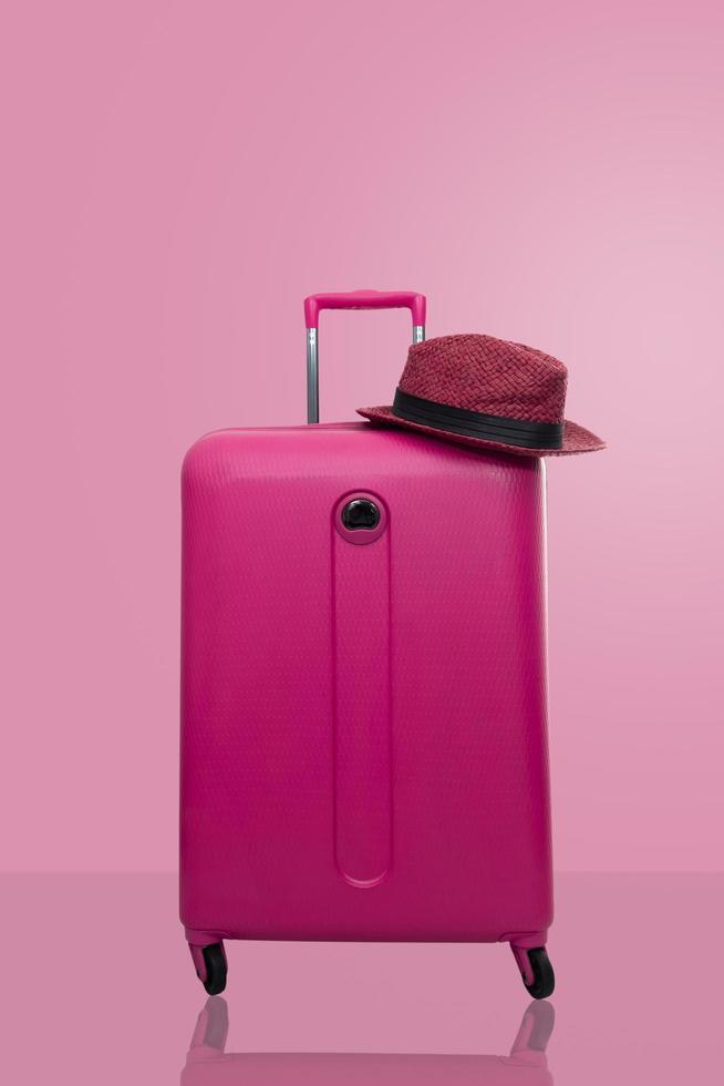 rosa Koffer mit Hut foto