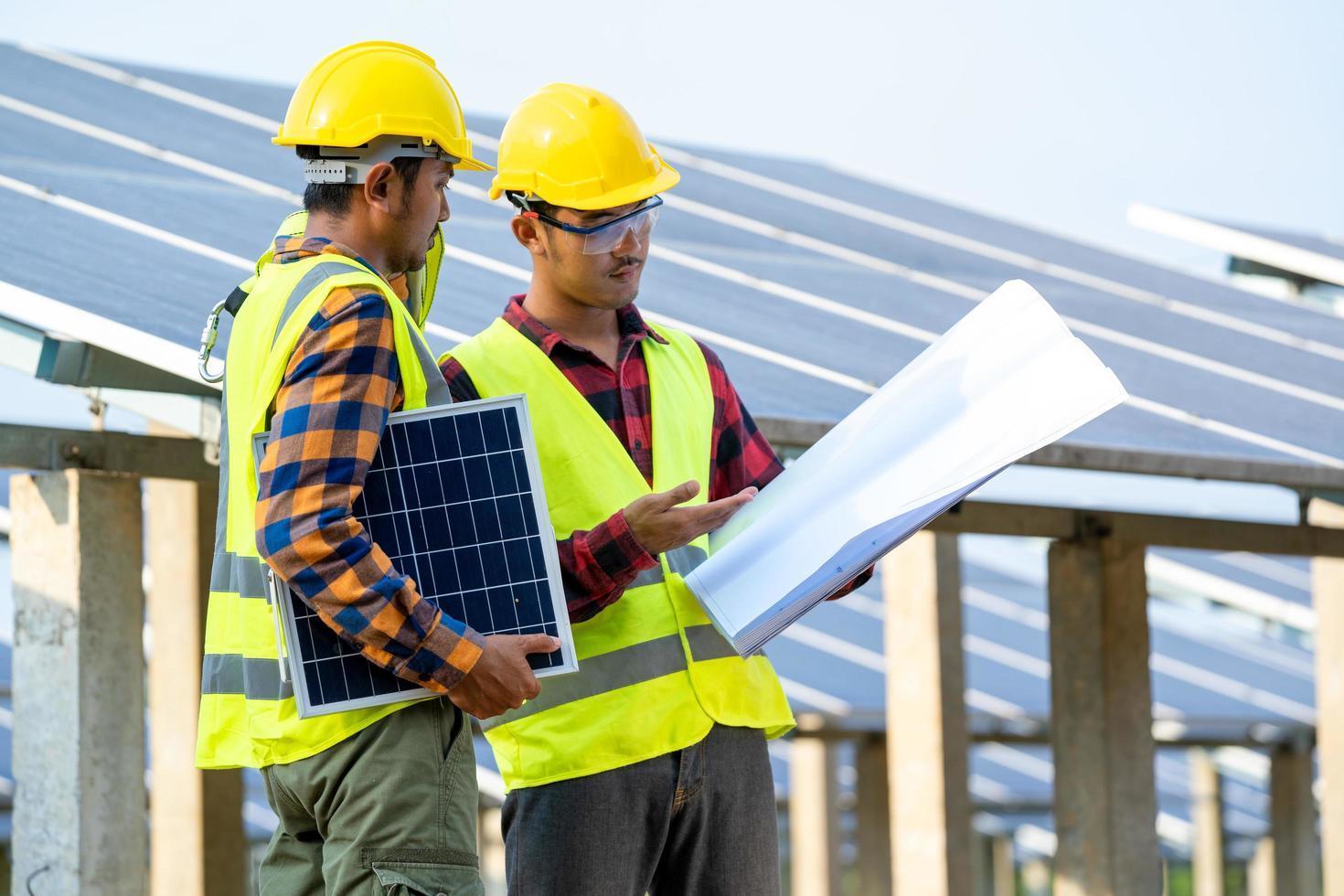 Männer, die Sicherheitsausrüstung neben Sonnenkollektoren tragen foto