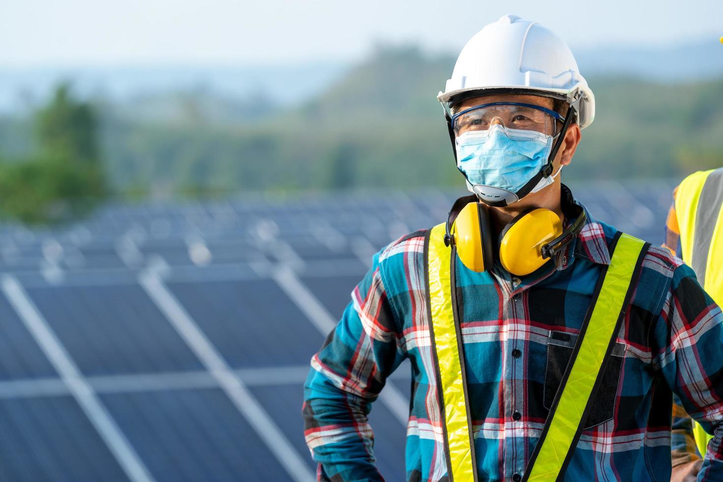 Mann trägt Sicherheitsausrüstung neben Solarpanel foto