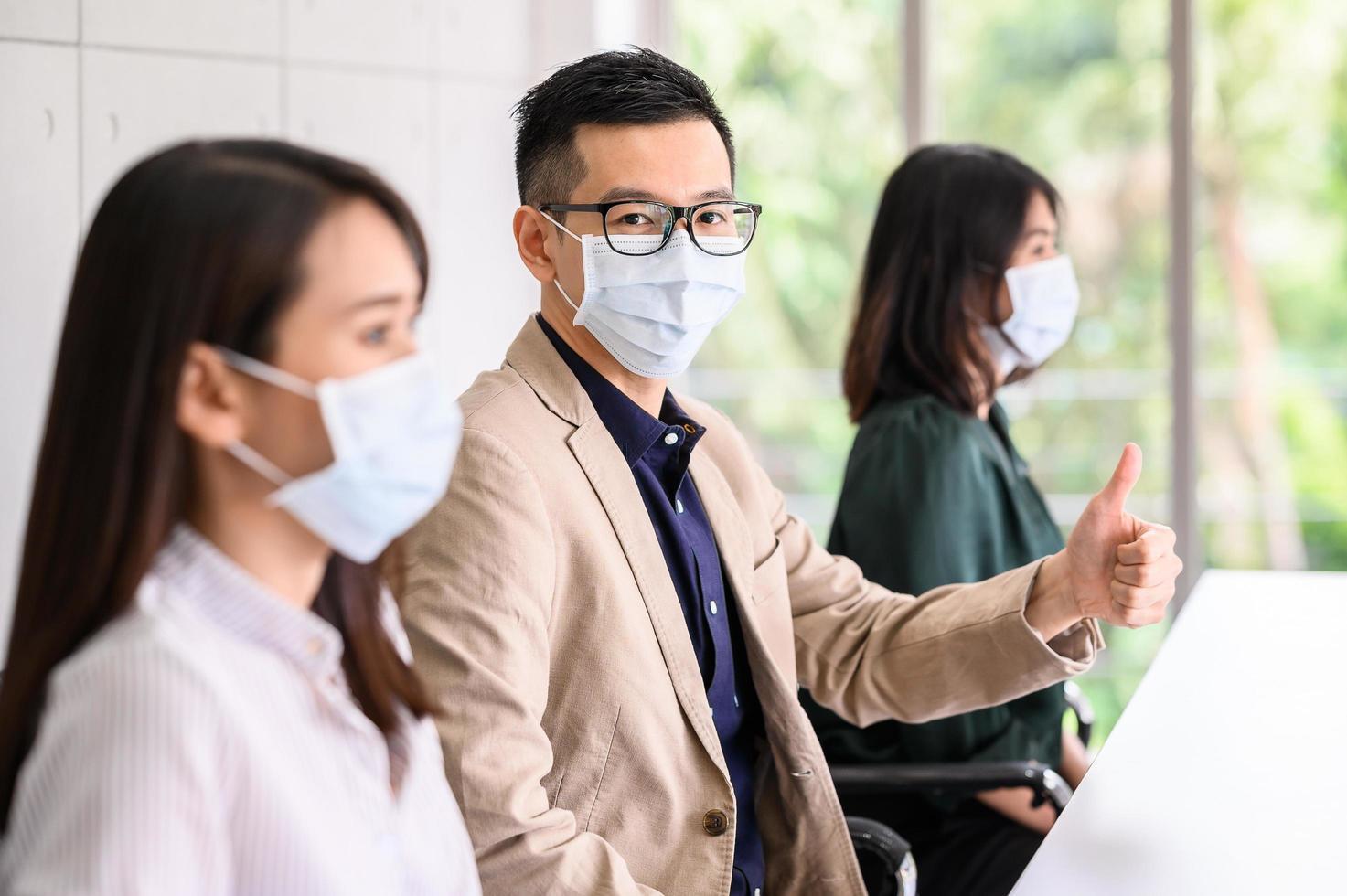 Reihe von Personen, die aus Sicherheitsgründen Gesichtsmasken tragen foto