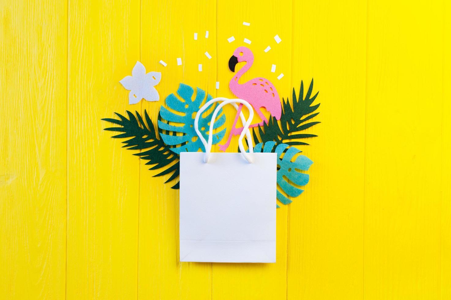 Modell des leeren Papiers mit Blättern und Flamingo auf gelbem hölzernem Hintergrund foto