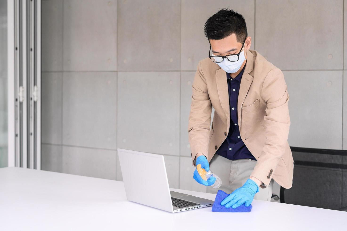Geschäftsmann, der Mikrofasertuch verwendet, um Laptop und Tisch zu reinigen foto