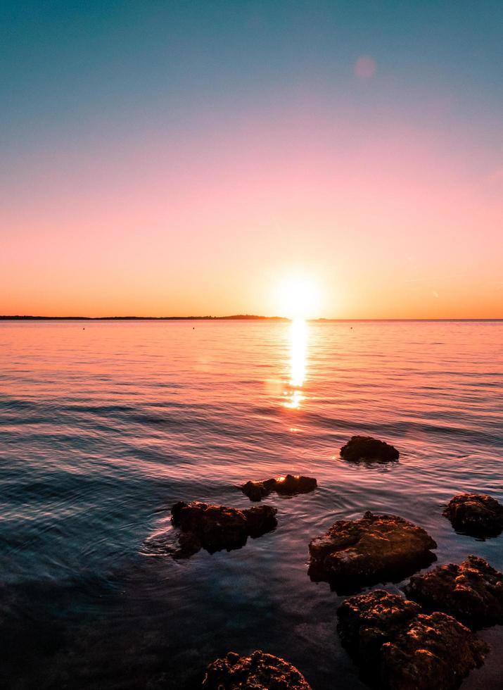 Felsen auf dem Wasser mit buntem Himmel foto