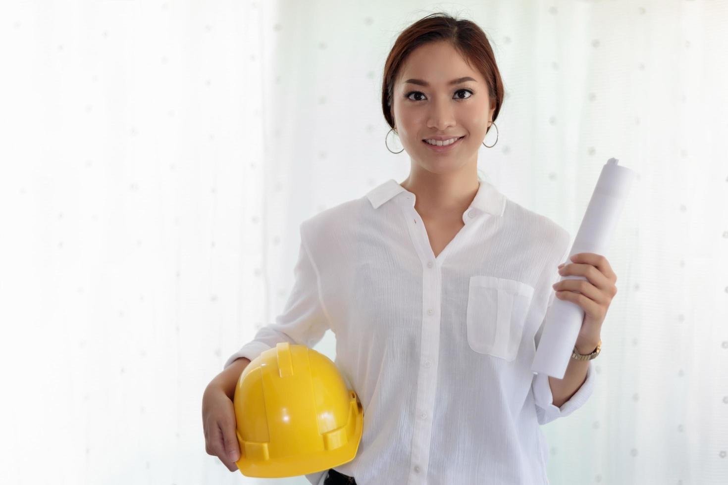 asiatische Frau, die Blaupausen und Schutzhelm hält foto