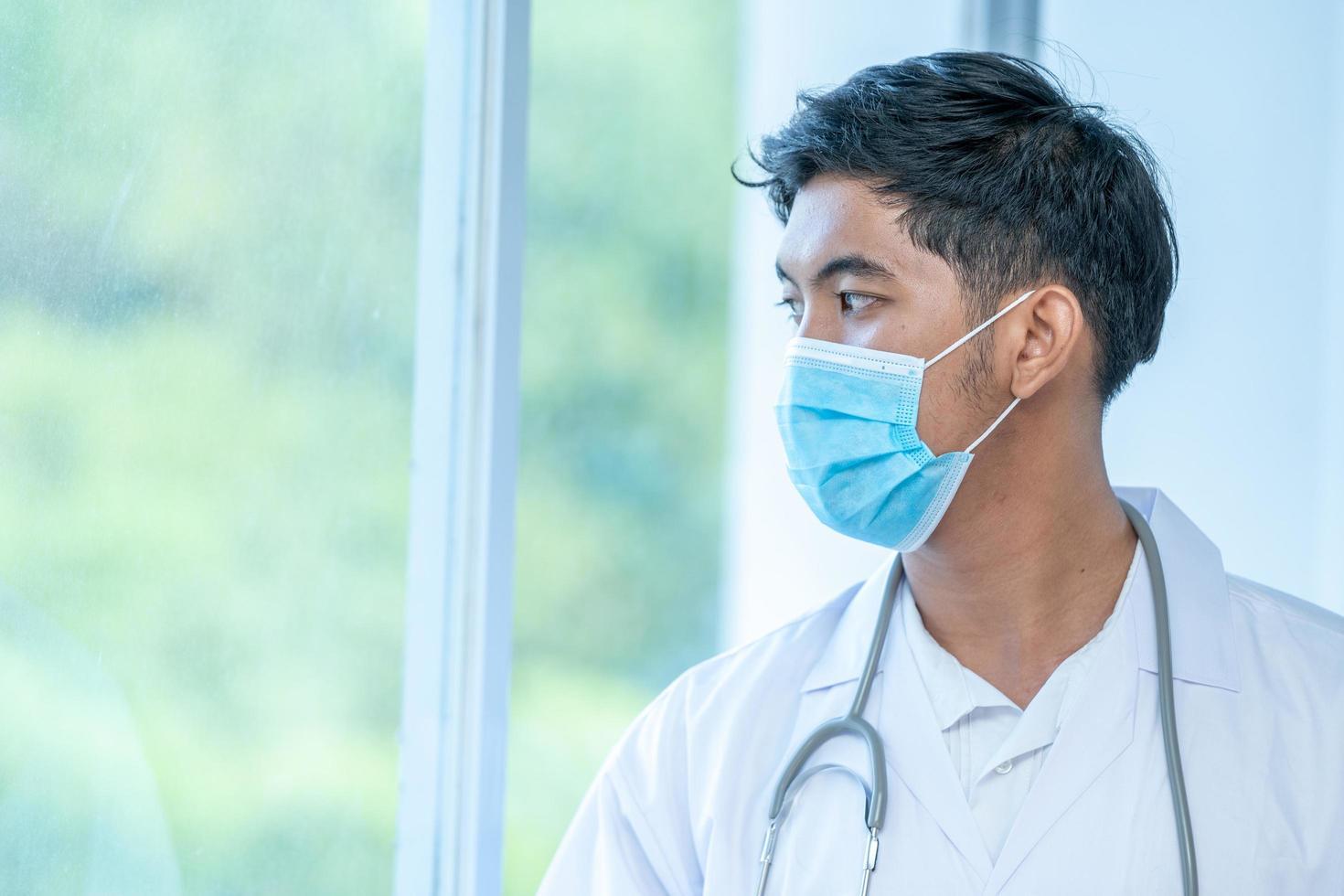 Mann mit Gesichtsmaske und Stethoskop aus dem Fenster schauend foto