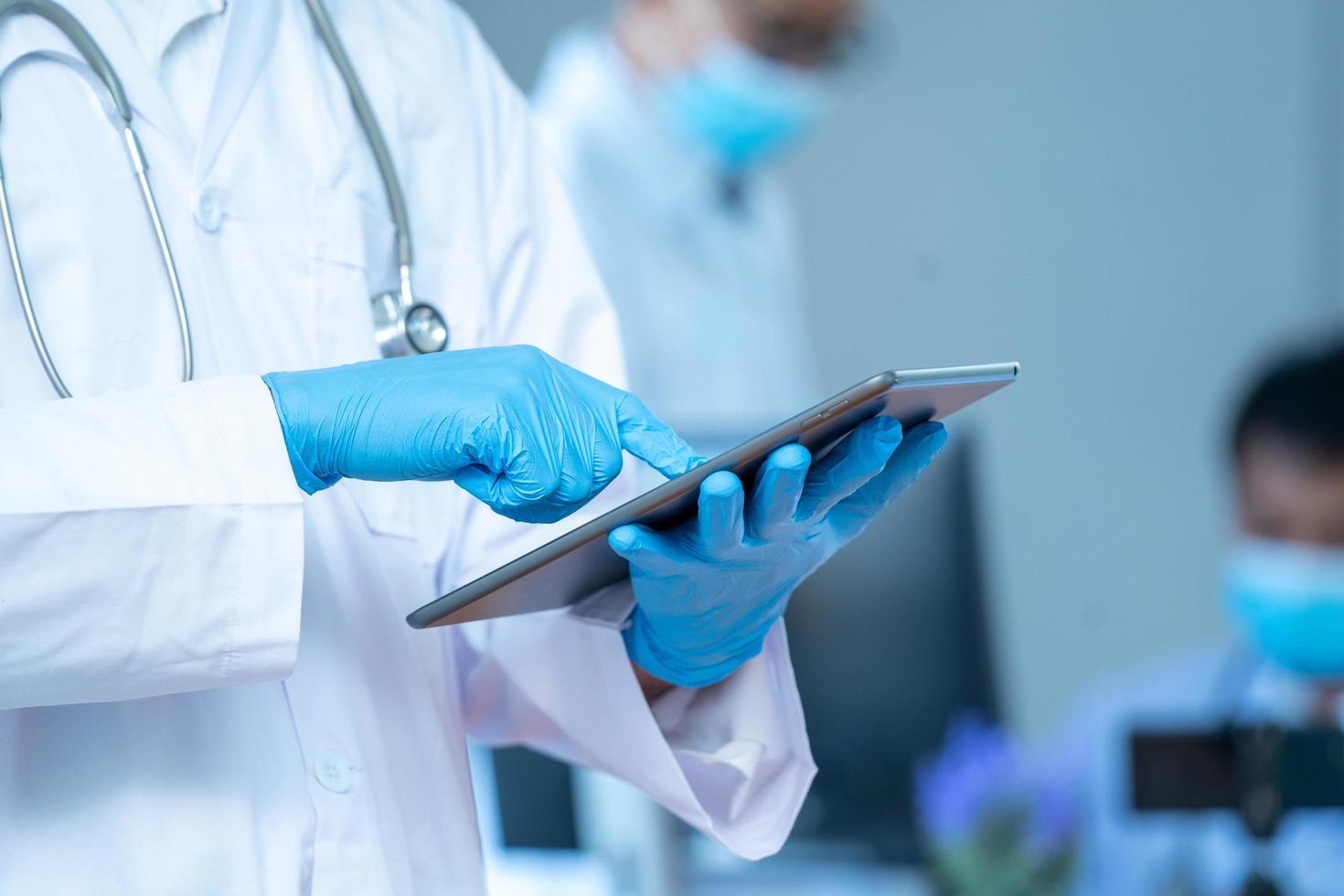Person mit Handschuhen und Laborkittel und Tablette foto