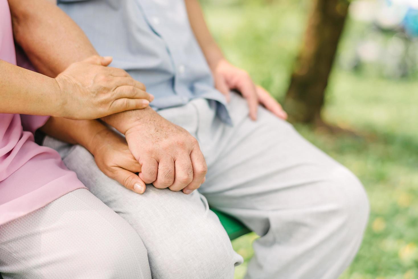 älteres Paar Händchen haltend im Sitzen foto