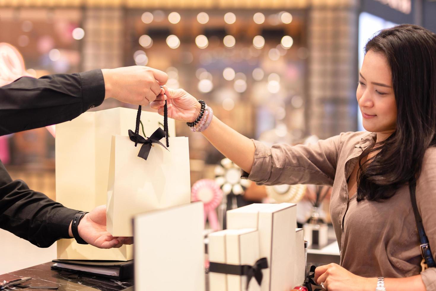 Verkäufer gibt dem Kunden die Einkaufstasche foto