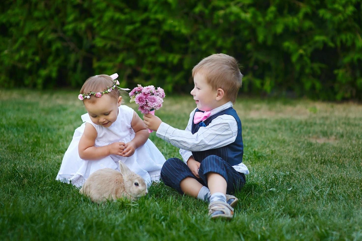 Junge gibt jungem Mädchen einen Blumenstrauß foto