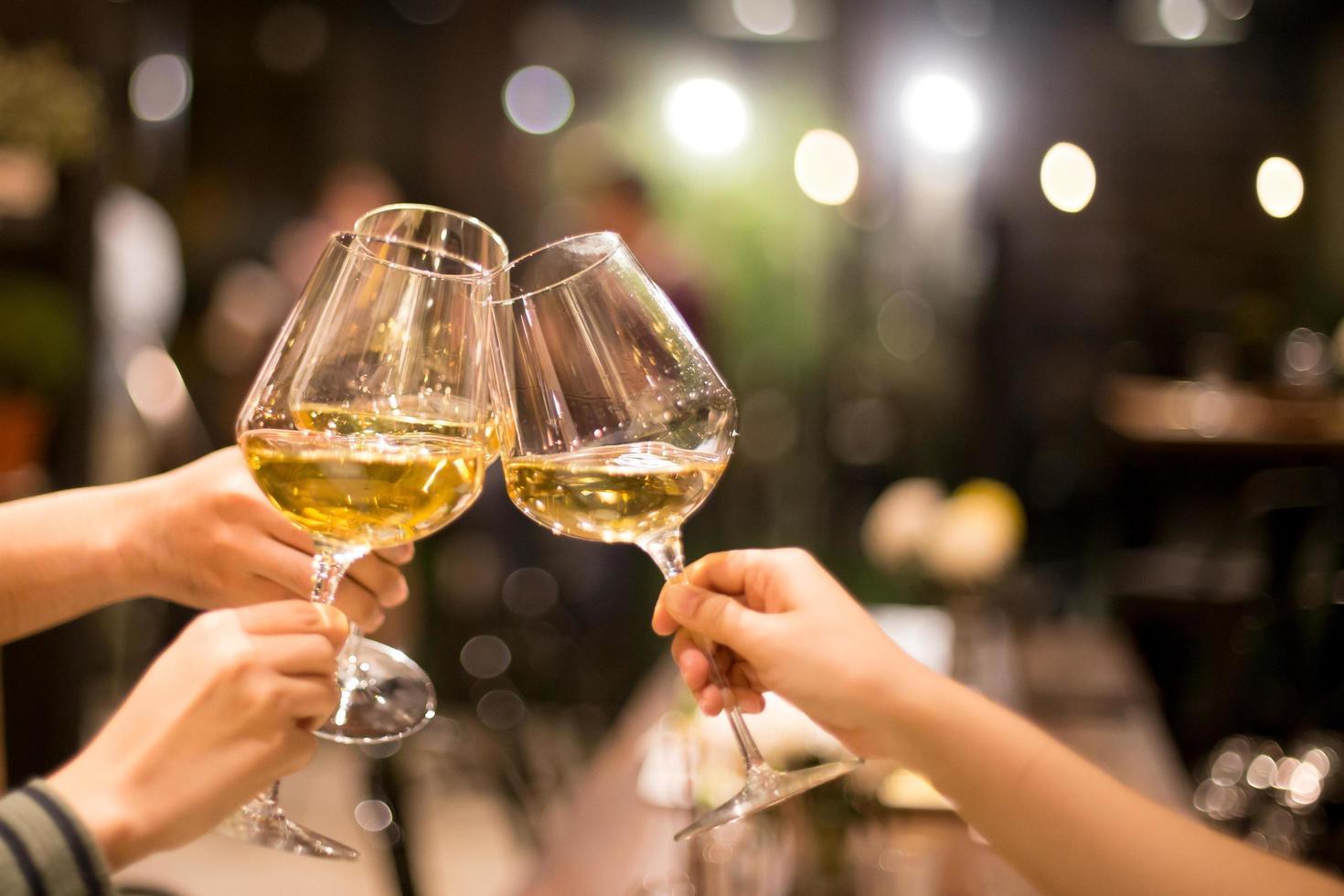 Freunde rösten mit Gläsern Wein foto