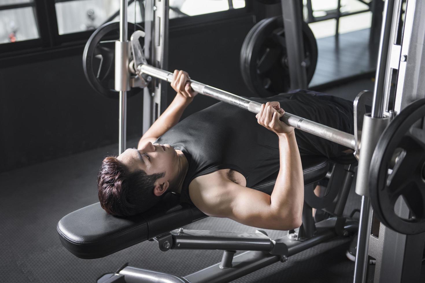 Mann auf Bankdrücken im Fitnessstudio foto