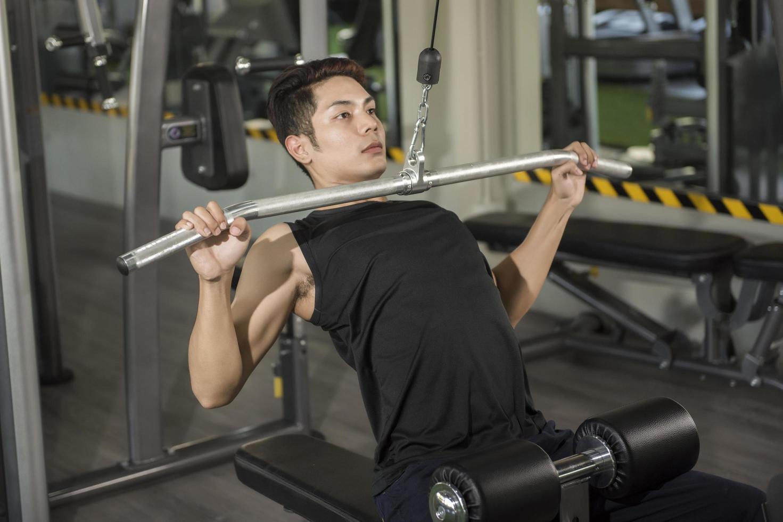 Mann, der auf einer Maschine im Fitnessstudio trainiert foto