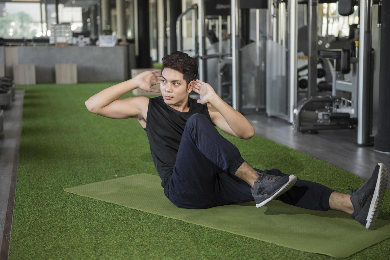 Mann macht Cruches in einem Fitnessstudio foto