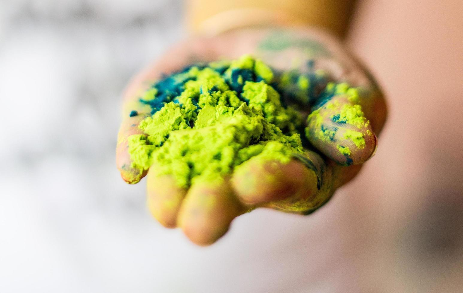 Person, die grünes Pulver hält foto
