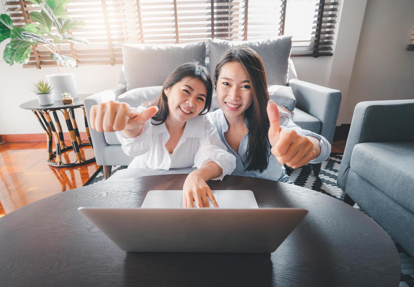 asiatische Freundinnen mit Laptop geben Daumen hoch Geste foto