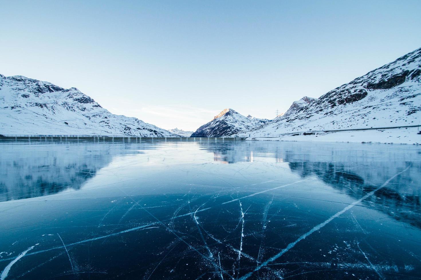 gefrorener Fluss mit schneebedeckten Bergen foto