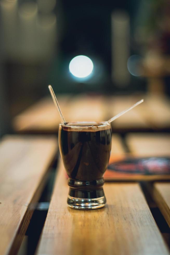 mit zwei Strohhalmen auf Holztisch trinken foto
