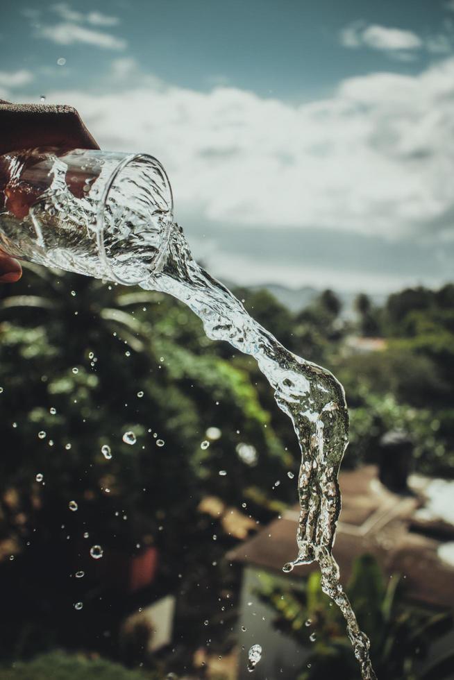 eine Person, die ein Glas Wasser einschenkt foto