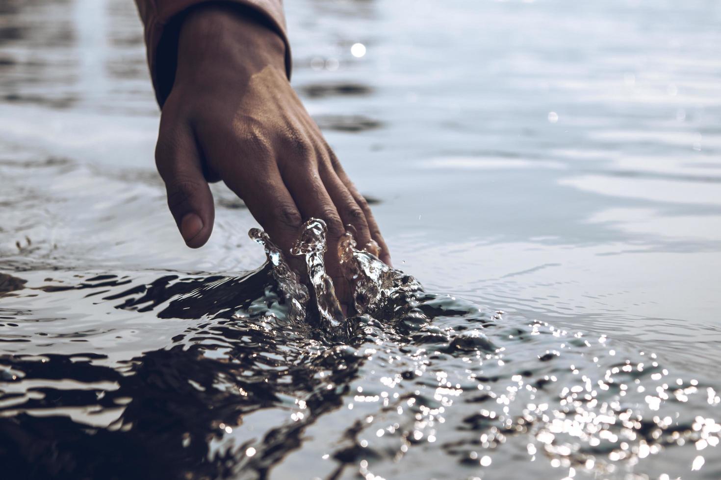 Nahaufnahme einer Hand, die durch Wasser läuft foto