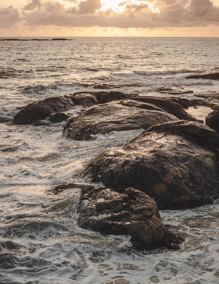 braune Felsformation auf Meerwasser foto