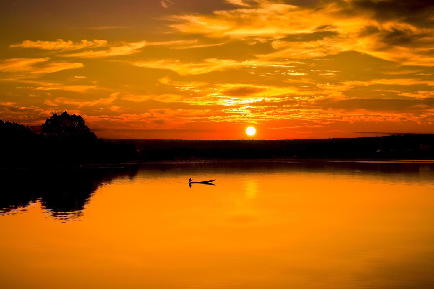 Mann und Boot auf dem Wasser bei Sonnenuntergang foto