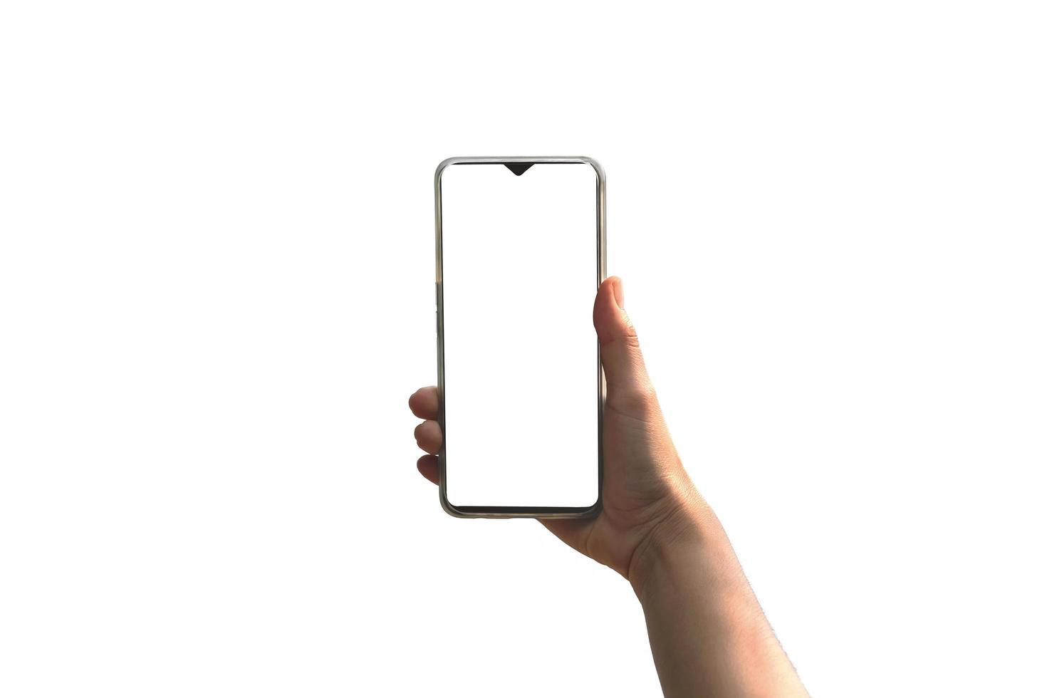 menschliche Hand, die ein Smartphone mit einem leeren weißen Bildschirm auf einem weißen hält foto