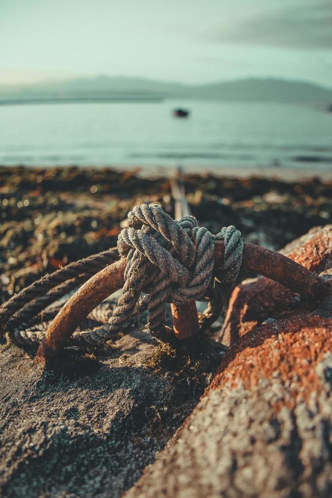 Seil an Felsen in Knoten in Strandnähe gebunden foto