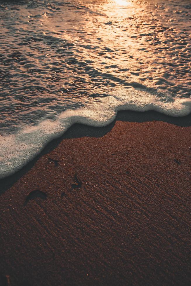 schaumiges Wasser fließt auf Sand und Strand foto