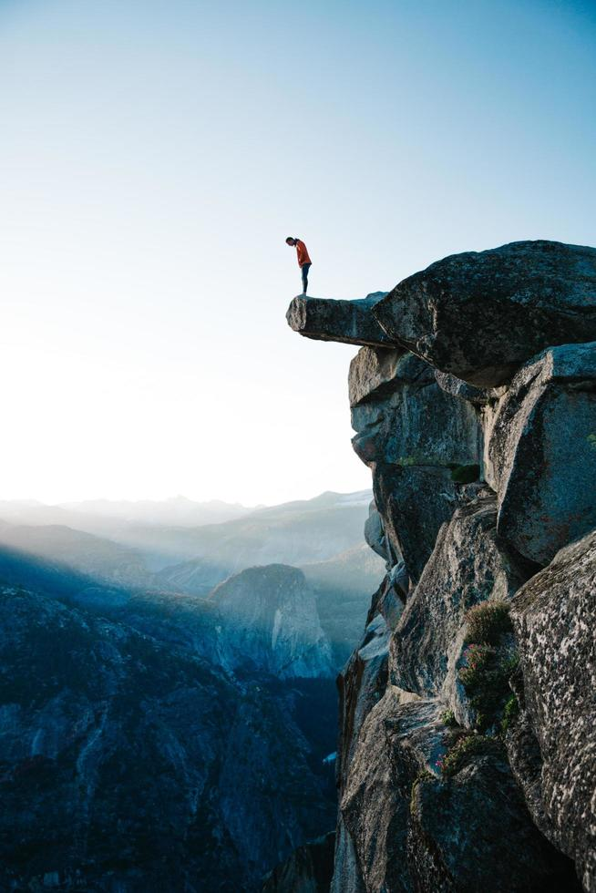 Mann stehend auf Klippe mit Blick auf Yosemite foto