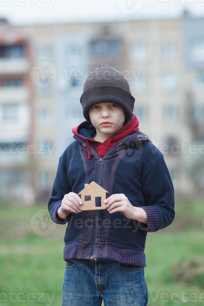 Obdachloser, der ein Papphaus hält foto