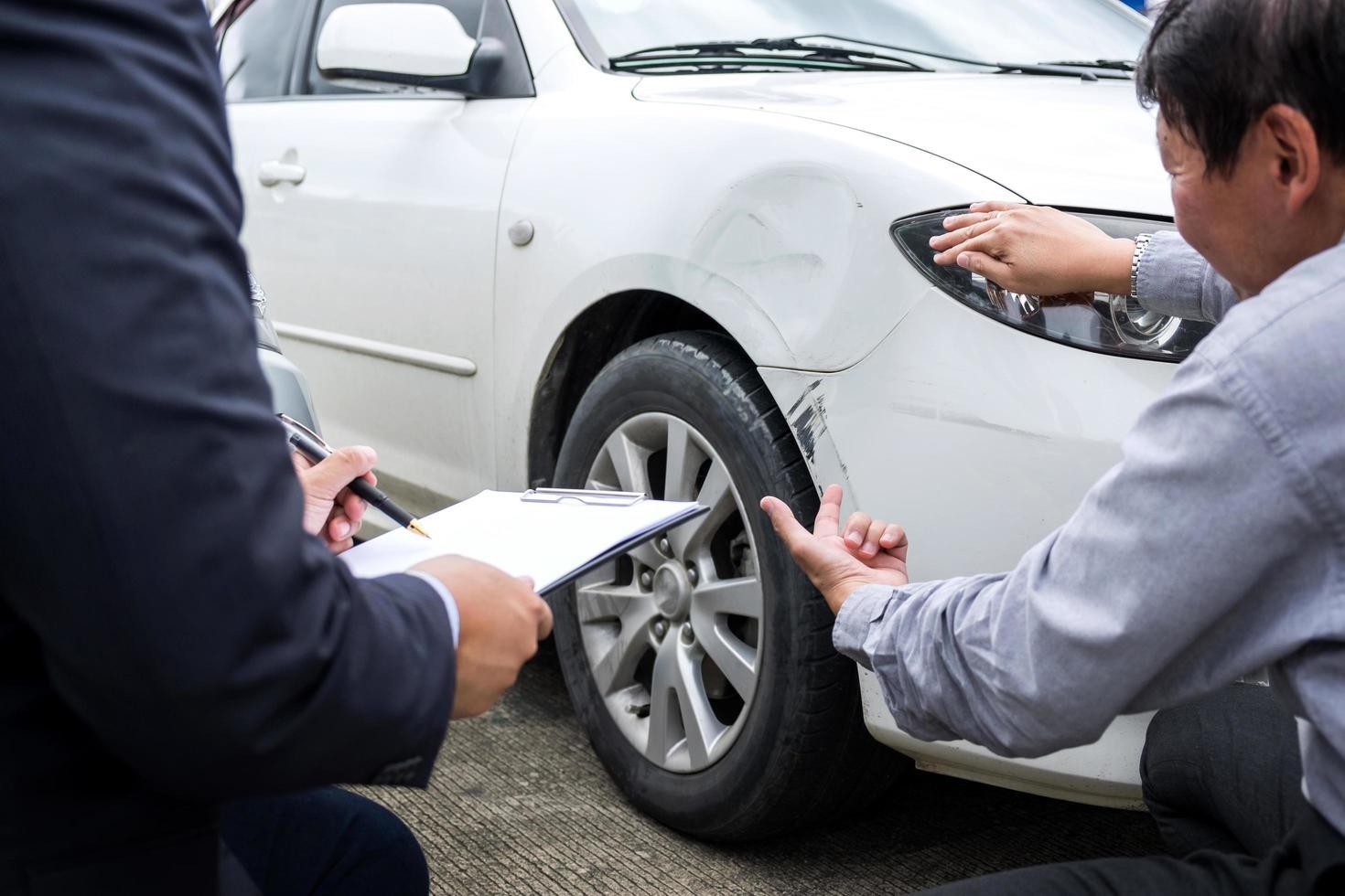 Agent, der das Versicherungsformular in der Nähe eines beschädigten Autos einreicht foto