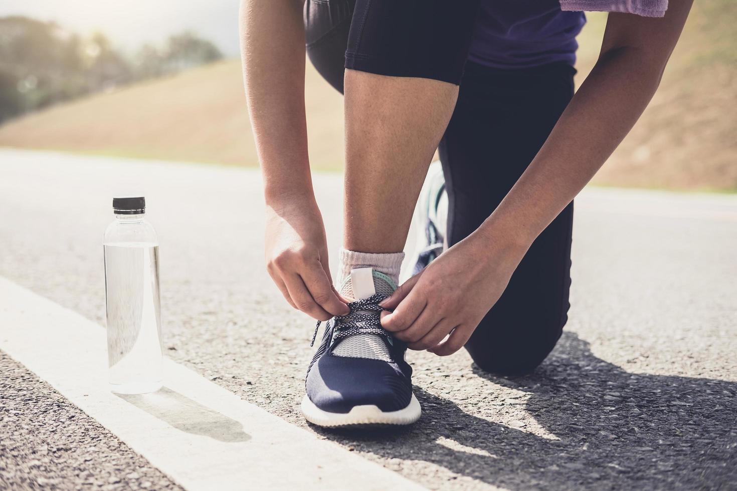 gesunder Lebensstil, Läufer, der Laufschuhe bindet, die sich für Rennen auf Laufstrecke Jog Workout Wellness-Konzept vorbereiten foto
