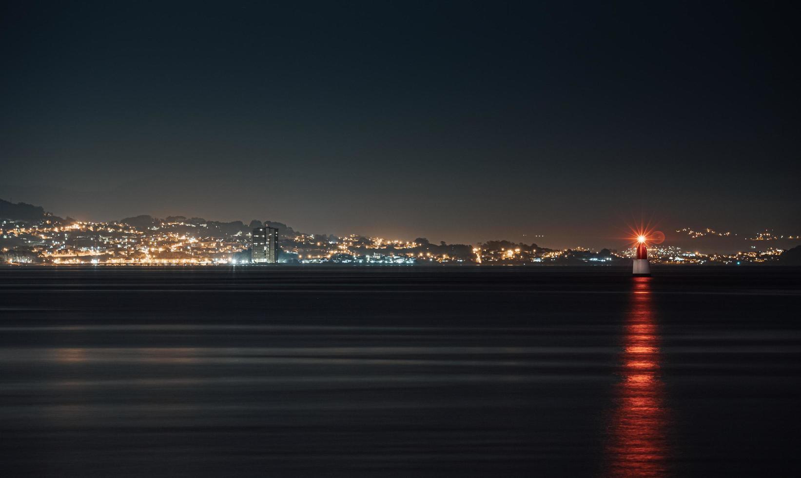 roter Leuchtturm mitten im Meer foto