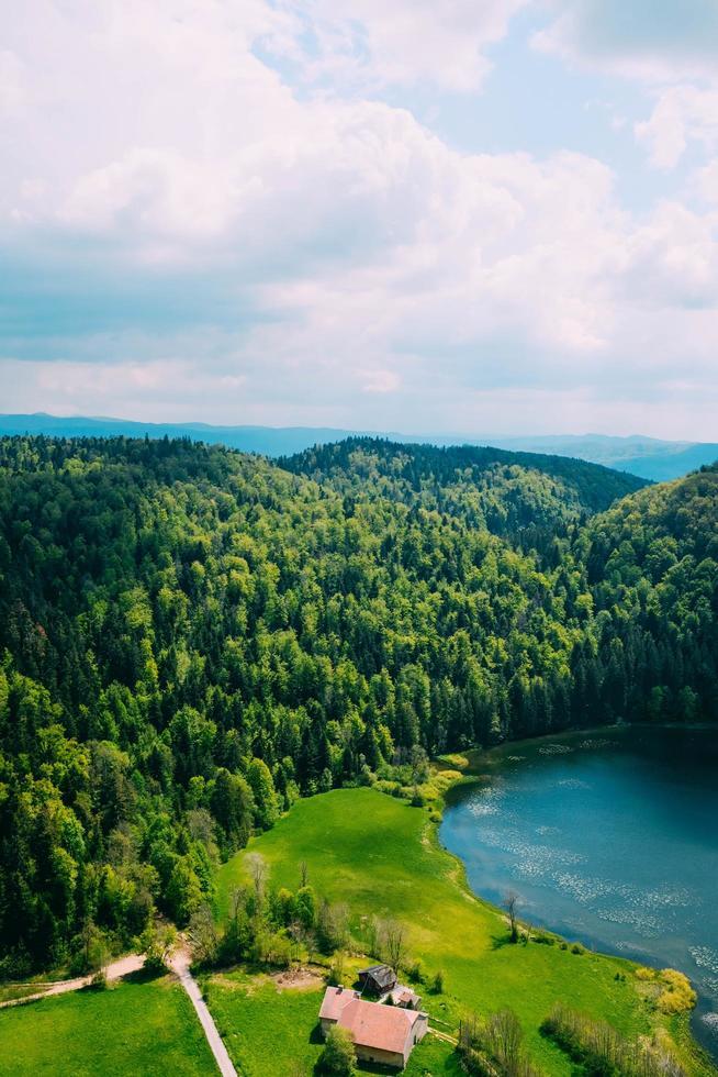 Haus am See und Wald mit bewölktem blauem Himmel foto