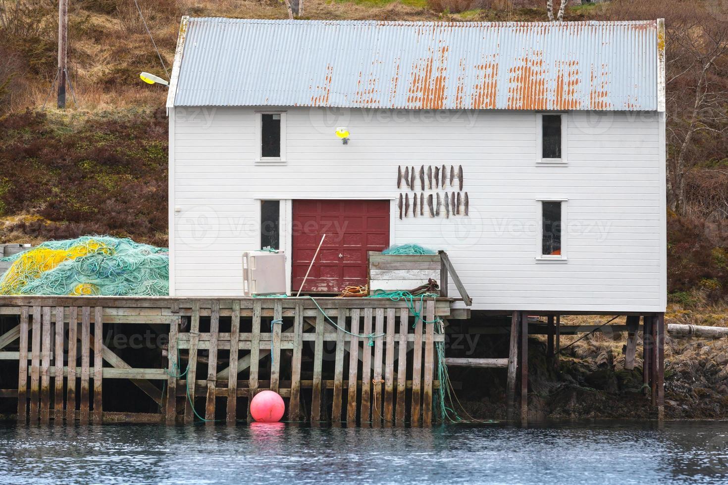 weiße hölzerne Fischerscheune mit Stockfisch foto