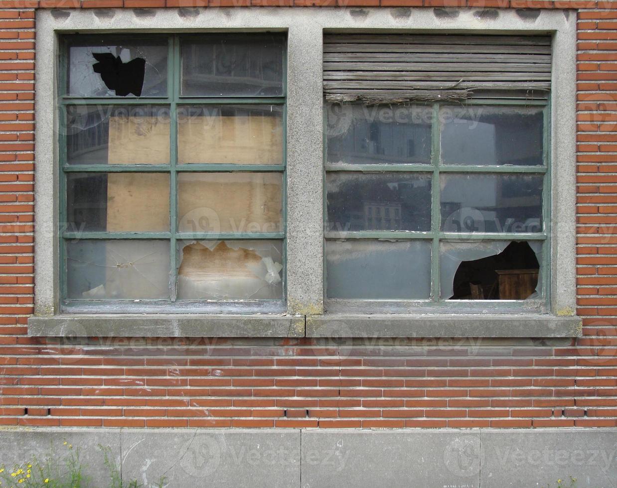 Fassade eines verlassenen Gebäudes mit zerbrochenen Fenstern und Rollladen foto
