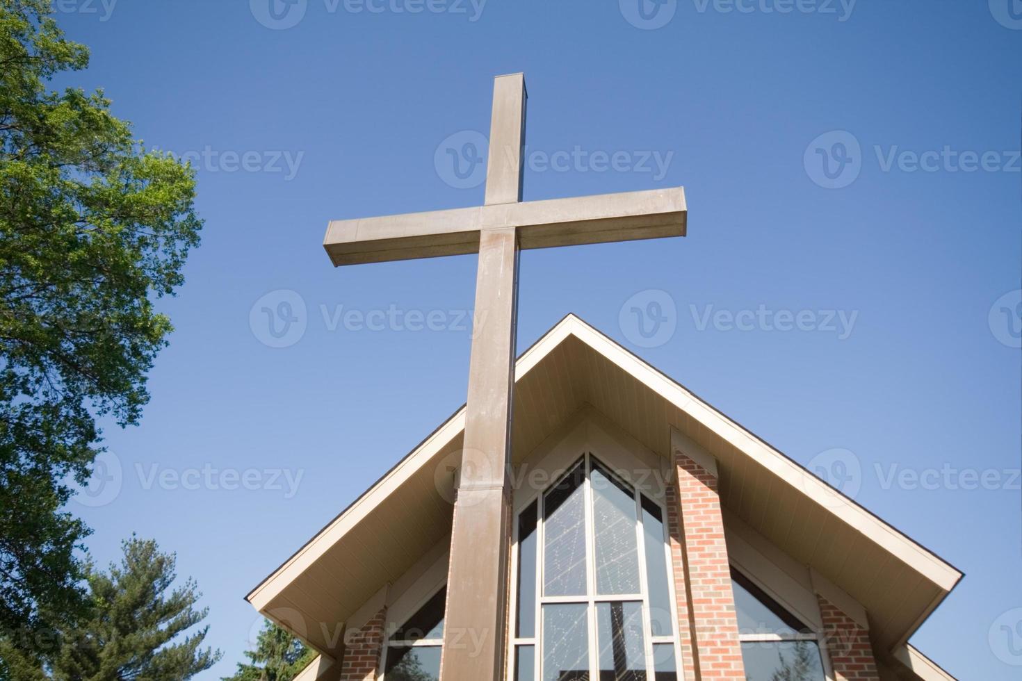 Weitwinkel des hohen Kreuzes mit moderner Kirche im Hintergrund foto