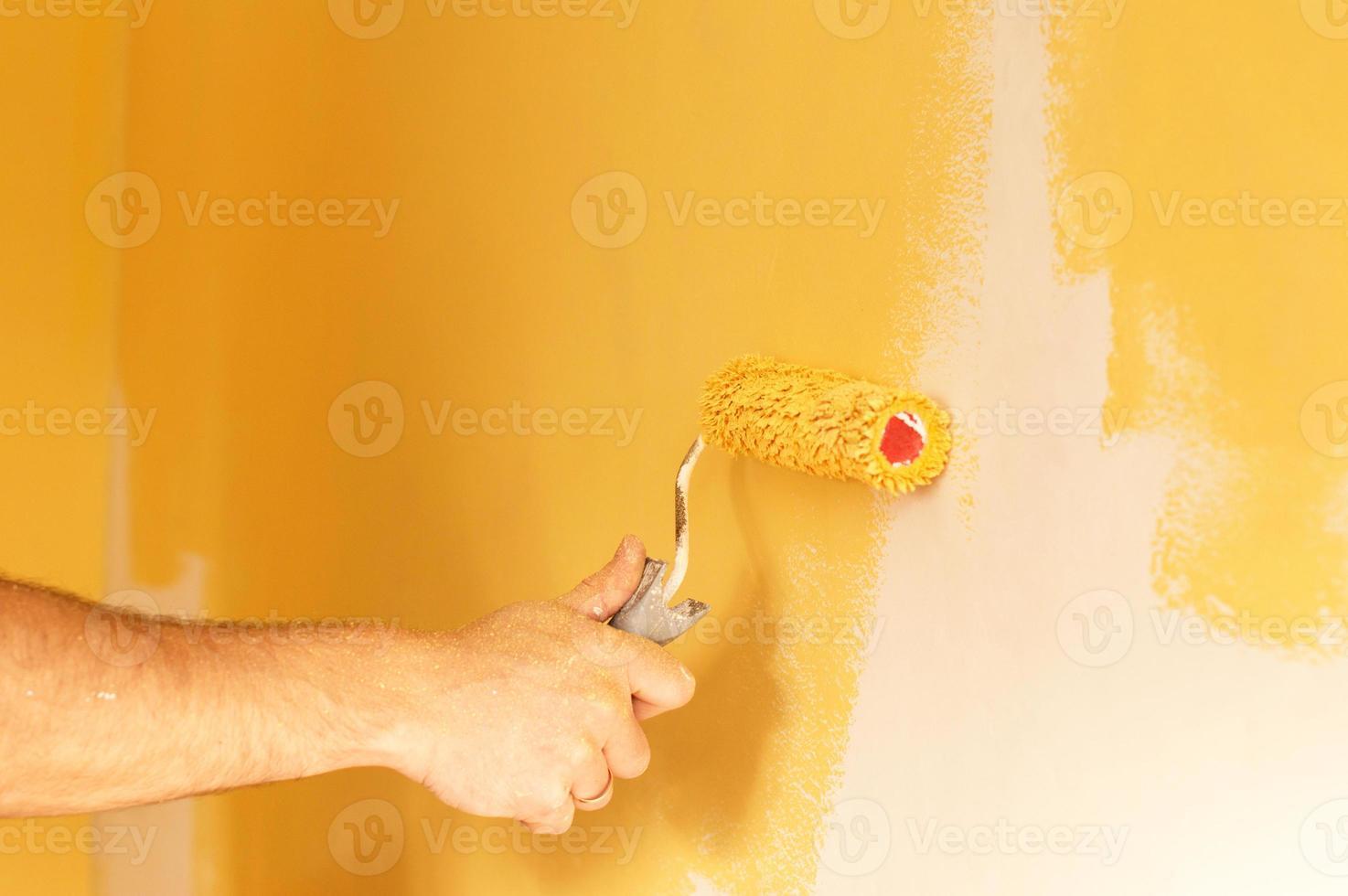 der Prozess des Malens der Wände in gelber Farbe foto