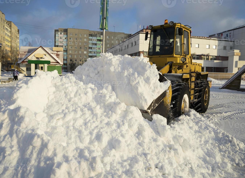 Traktor schaufelt Schnee in Haufen auf der Straße. foto