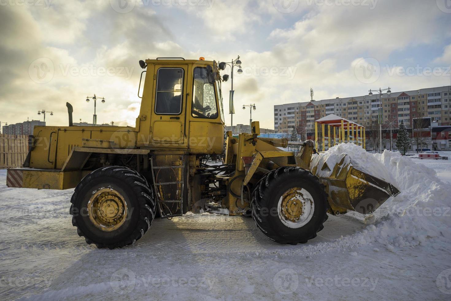Traktor schaufelt Schnee in einem Haufen auf der Straße. foto