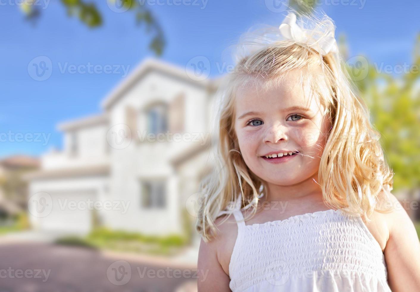 süßes lächelndes Mädchen, das im Vorgarten spielt foto
