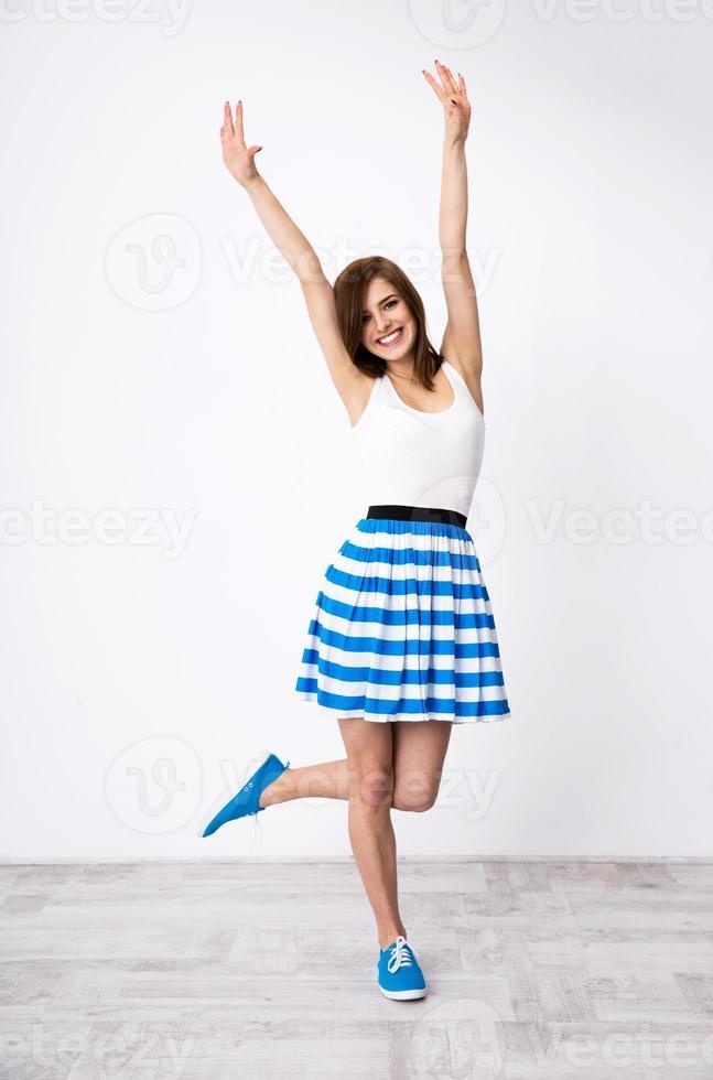 lächelnde Frau mit erhobenen Händen foto