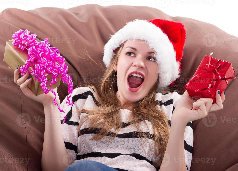 Mädchen sitzt auf einem Stuhl mit einem Geschenk in den Händen foto