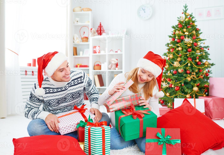 glückliches Familienpaar mit einem Geschenk an Weihnachten zu Hause foto