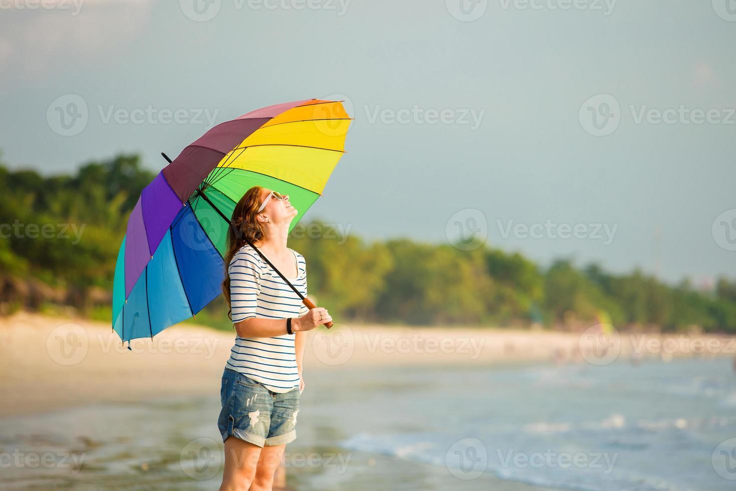 attraktive kaukasische Frau, die Sonnenbrille hält, die bunten Regenbogenschirm-Strand hält foto
