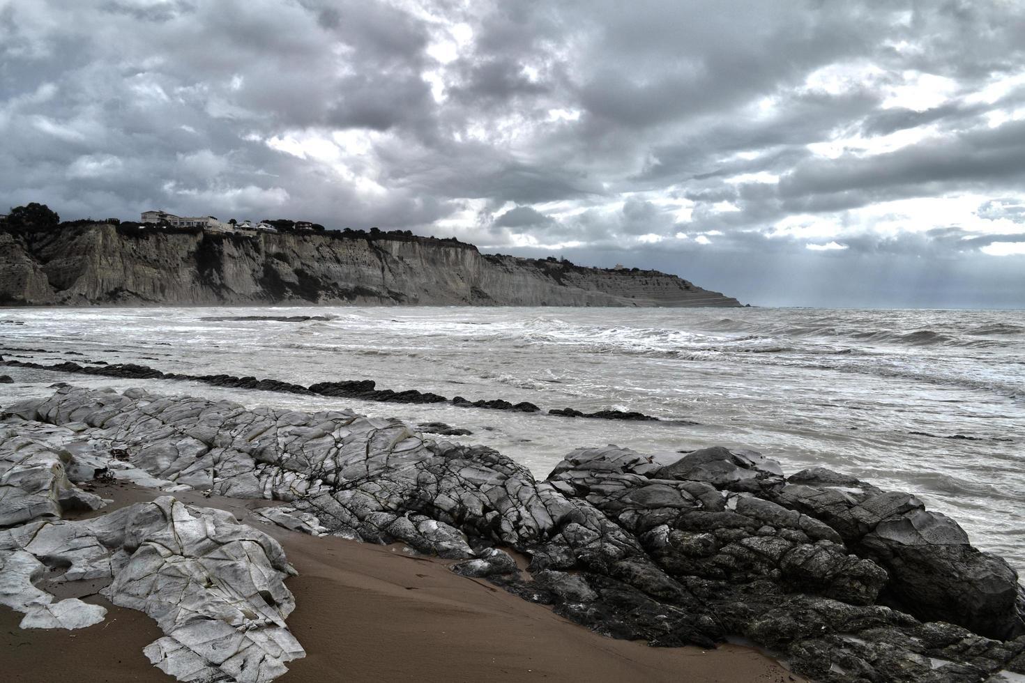 graue Felsen nahe Meer unter grauem Himmel foto