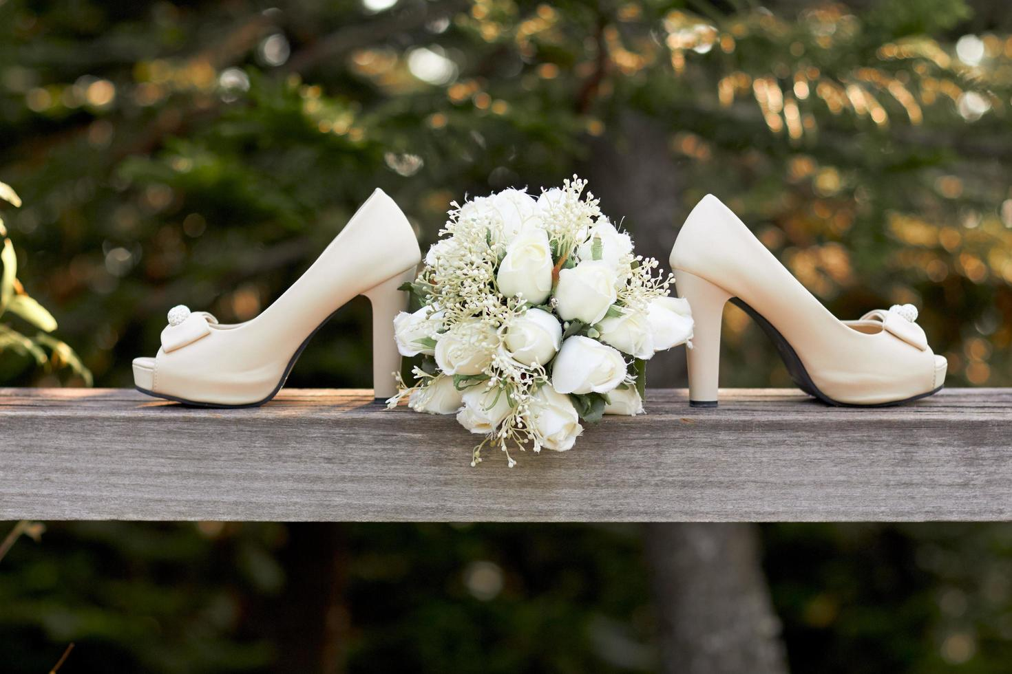 Hochzeitsschuhe und Blumenstrauß draußen foto
